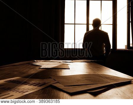 Overworking. Tired Businessman Looks Out The Office Window At The Setting Sun.