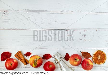 Composition Of Several Ripe Red Apples, Glass Bottle And Autumn Leaves On A Light Surface. Apple Cid