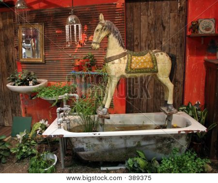 antique wooden horse set in old bathtub and surrounded by greenery poster