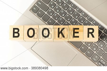 Word Booker. Wooden Cubes With Letters Isolated On A Laptop Keyboard. Business Concept Image.