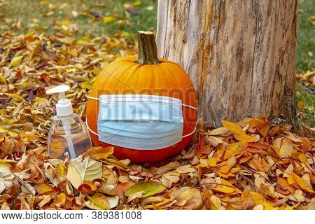 A Pumpkin Wearing A Facemask With A Hand Sanitizer Bottle Next To With Leaves During Fall. Concept H
