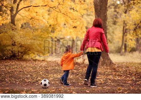 Mother And Son Walk Holding Hands In Autumn Park. Soccer Ball Laying Forgotten Behind Them. Mom Taki