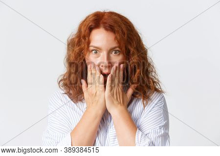 People, Emotions And Lifestyle Concept. Close-up Of Gasping, Shocked Middle-aged Redhead Woman Holdi