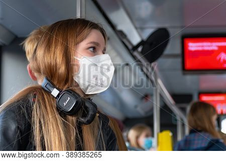 Vilnius, Lithuania - October 12 2020: Pretty Young Girl With Mask And Earphones Or Headphones In A B