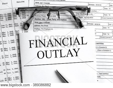 Paper With Text Financial Outlay On A Financial Table With Eyeglasses And Metal Pen