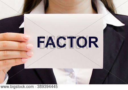 The Word Factor Is Written On A White Piece Of Paper Which Is Being Held By A Businesswoman. The Wor