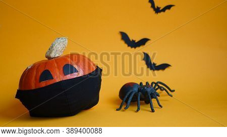 Halloween Pumpkin In Black Medical Mask,spider And Bats On Orange Background.concept Championed Hall
