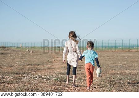 Two Poor Children Family Brother With Toy And Thin Sister Refugee Illegal Immigrant Walking Barefoot