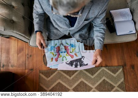 Top View Of Psychologist Choosing Picture With Ink Stain, Rorschach Inkblot During Therapy Session.