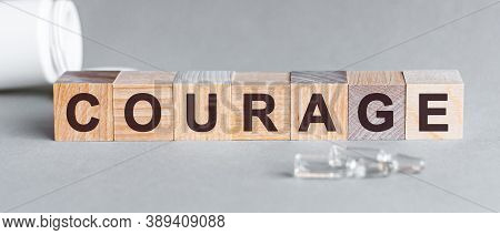 Word Courage. Courage Text On Wooden Blocks. In Front Of A Row Of Cubes Are Ampoules, In The Backgro