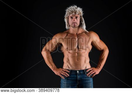 Bodycare With Fitness And Sport. Man With Muscular Torso. Bodybuilder In Fur Hat And Jeans Dark Back