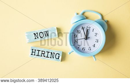 New Hiring Text Written On Wood Block. Now We Are Hiring Text On The Yellow Table With A Blue Alarm
