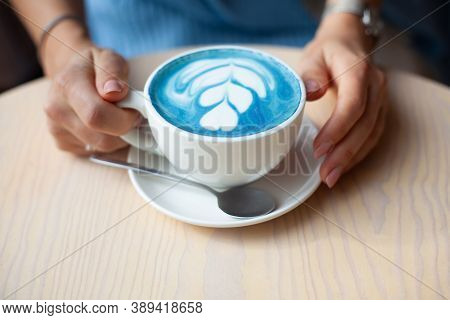 Unfocused Woman Hands Holding Cup Of Hot Butterfly Pea Latte Or Blue Spirulina Latte On Wooden Table