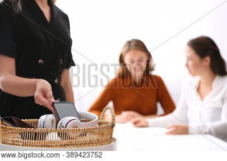 Woman Putting Smartphone Into Wicker Basket With Gadgets In Office, Closeup. Digital Detox Concept