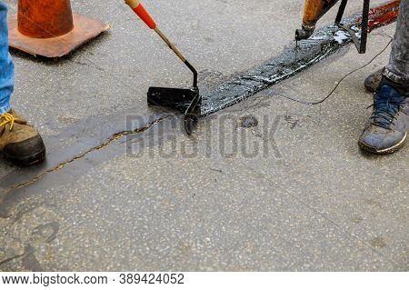 Road Surface Restoration Work In The Worker Performs On Road Patcher Work On The Repair Of Cracks By