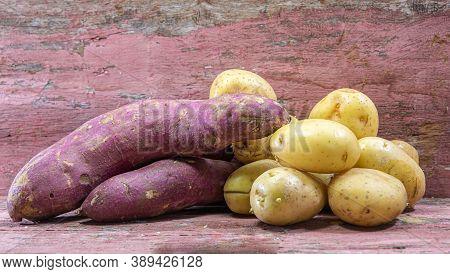 Sweet Potato (ipomoea Potatoes) And White Potato (solanum Tuberosum) On The Old Wooden Background