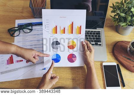 Woman Working At Home Office Desk Using Laptop Business Financial Document Chart And Graph On Wooden