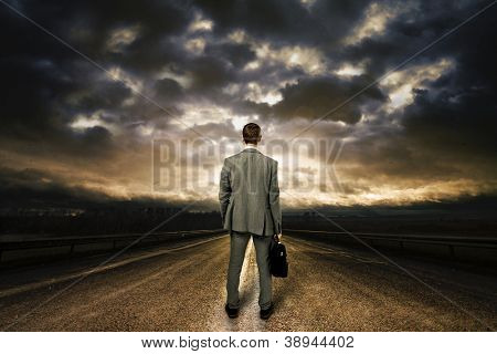 Business man standing in the middle of the road. Dramatic sky above