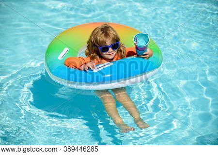 Happy Kid Playing With Swim Float Ring In Swimming Pool. Summer Vacation. Healthy Child Lifestyle