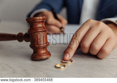 Husband Signing Divorce Contract. Mans Hand, Wooden Gavel And Rings Close-up. Divorce And Separation