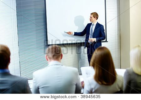 Confident businessman pointing at whiteboard while making speech at conference