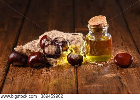 Chestnuts And Chestnut Oil On The Wooden Table.