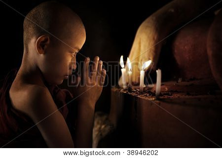 Little novice monk praying in front candlelight
