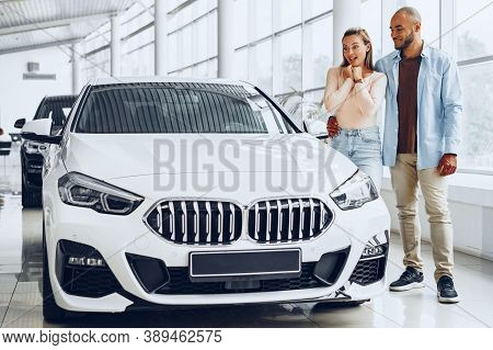 Young Happy Couple Choosing A Car In Car Dealership