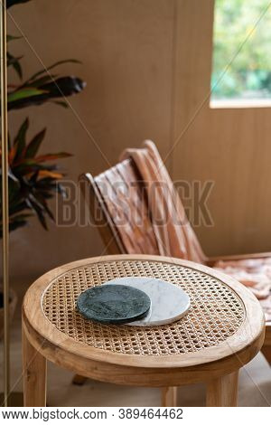 Stylish Living Corner Setting With Circular Marble Tray On Rattan Wood Table And Artificial Plant In