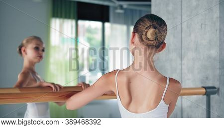 Cute Preteen Girl Ballerina With Bun In White Costume Looks Into Large Mirror Leaning On Wooden Barr