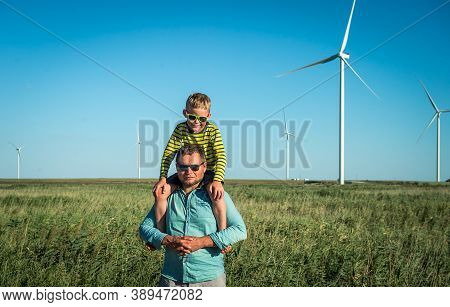 Wind Turbine Field. Father Carrying Son On Shoulders And Waving Their Arms Like A Windmill.
