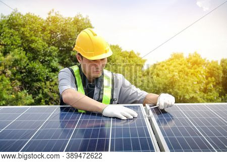 Asian Technicians Install Panels Solar Cells To Produce And Distribute Electricity. Energy Technolog