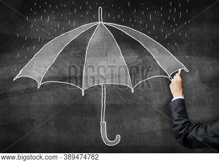 Businessman Hand With Chalk Draws Umbrella Sketch On Chalkboard. Freehand Illustration On Blackboard
