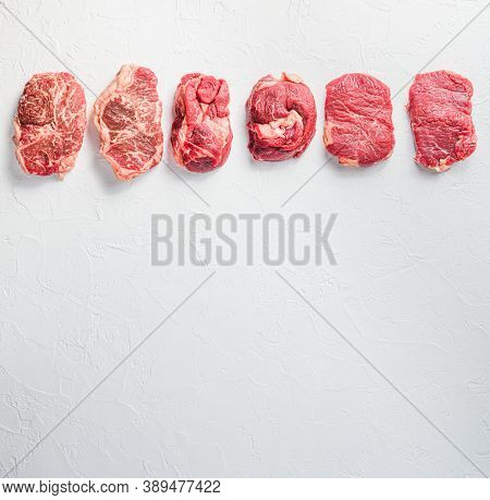 Rraw Beef Steaks Set Top Blade, Rump, Chuck Eye Roll Over White Concrete Background, Top View Space