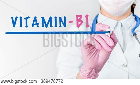 Close Up Female Doctor In A White Coat With Stethoscope And Pink Sterile Gloves Writing Word Vitamin
