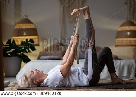 Woman Working Out, Warming Up Using Yogic Belt, Lying In Yoga Supta Padangushthasana, One Leg Lift E