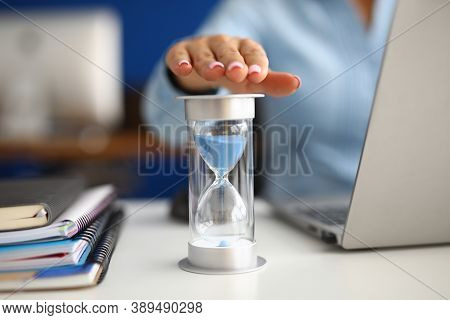 Woman Holds Her Hand Over Hourglass At Workplace In Office Closeup. Time Is Money Concept.