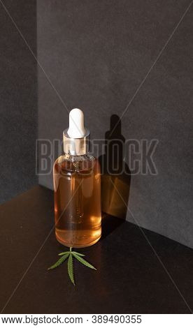 Glass Bottles And Dropper Cbd Oil, Thc Tincture And Cannabis Leafs On Black Background. Laboratory P