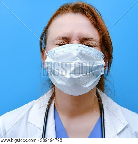 Doctor Woman On A Blue Background, Close-up. The Face Of A Nurse Girl With Squinted Eyes In A White