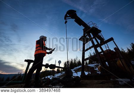 Low Angle Side View Snapshot Of Petroleum Engineer Wearing Orange Vest And A Helmet, Looking At The