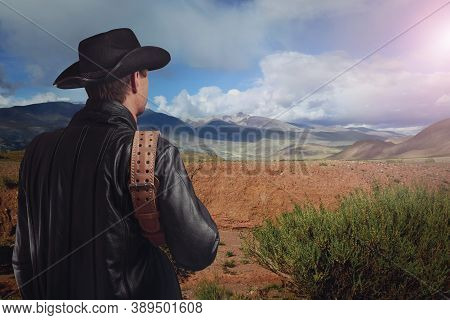 Cowboy Looks Into The Distance At The Mountains. Man In A Leather Coat And A Cowboy Hat Holds A Belt