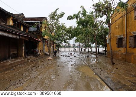 Hoi An, Vietnam, October 13, 2020: Workers Clean Street's Mud After Severe Flooding Due To A Tropica