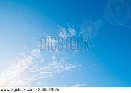 Blue sky background, white dramatic fluffy clouds lit by sunset light. Vast sky landscape scene, sky landscape, sunny sky background. Sky background, sky scene, colorful sky landscape