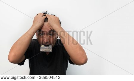 Portrait Of Stressed  Asian Man Trying To Find Money To Pay Credit Card Debt. Broke Man Serious Putt