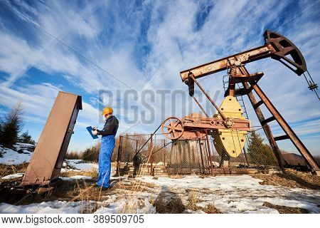 Petroleum Engineer In Work Overalls And Helmet Making Notes On Clipboard While Controlling Work Of O