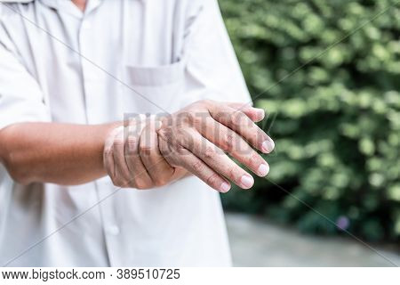 Patients Elderly Wrist Pain Hands, Due To A Nervous System Illness And Paralysis, On Blur Background