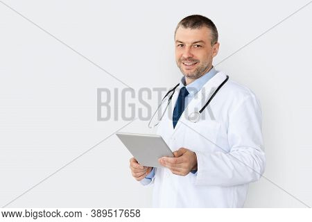 Medical Care And Technology Concept. Portrait Of Smiling Confident Doctor Using Digital Tablet, Stan