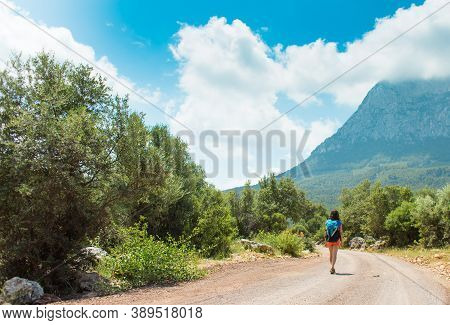 A Woman With A Backpack Is Walking Along A Mountain Road, Girl On A Background Of Beautiful Mountain