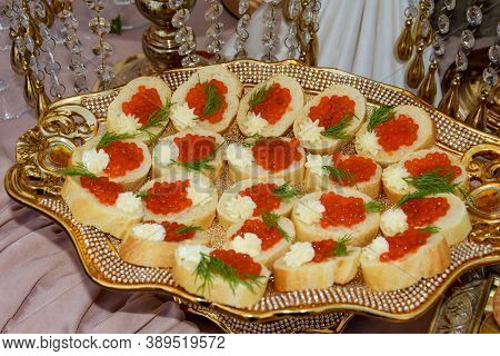 Sandwiches With Caviar And A Piece Of Butter Lie On A Gold Tray. Sandwiches Or Canapes With Red Cavi