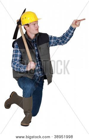 Tradesman holding a pickaxe and pointing his finger